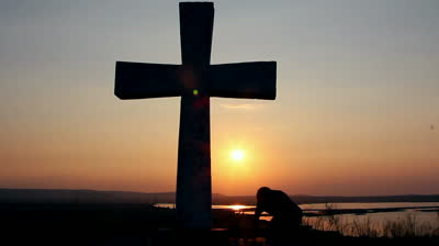 stock-footage-silhouette-of-man-praying-under-the-cross-at-sunset-sunsrise